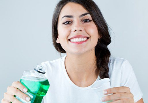 Woman smiling and holding mouthwash